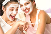 Caucasian girls wearing peeling mask having fun — Stock Photo