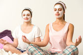Meditating women wearing white facial mask — Stock Photo