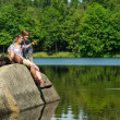 Young couple sitting on rock by the lake — Stockfoto