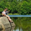 Young couple sitting on rock by the lake — Stok fotoğraf