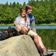 Stockfoto: Young couple hikers lounging at lake nature