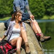 Young trekking couple resting at lakeside — Stockfoto