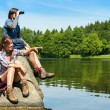 Teenage hikers birdwatching at lake — Stock Photo #27295585