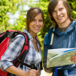 Portrait of trekking couple checking the map — Stock Photo #27295603