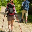 Young tourists with trekking poles in woods — Stock Photo #27295611