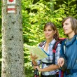 Stock Photo: Young tourists checking map and blaze