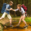 Hiker boy help trekking girl crossing creek — Photo
