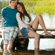 Teen couple sitting on water pier — Stock Photo
