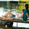 Caucasicouple lounging on pier sunset — Stockfoto #27295683
