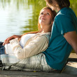 Romantic couple lounging on pier — Stock Photo #27295687