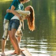 Playful couple having fun on pier lake — Stock Photo