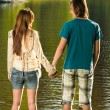 Teenage couple standing in water holding hands — Stock Photo #27295721