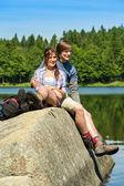 Caminhantes do jovem casal descansando na natureza do lago — Foto Stock