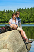 Young couple hikers lounging at lake nature — Photo
