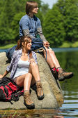 Young trekking couple resting at lakeside — Stock Photo