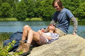 Trekking couple resting at lakeside — Stock Photo