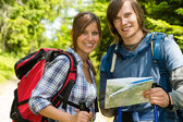 Portrait of trekking couple checking the map — Stock Photo