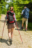 Young tourists with trekking poles in woods — Stock Photo