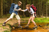 Hiker boy help trekking girl crossing creek — Stock Photo