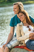 Smiling teen couple sitting on a rock — Stock Photo