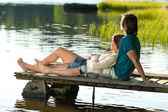 Caucasian couple lounging on pier sunset — Stock Photo
