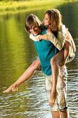 Girl piggyback riding his boyfriend in water — Stock Photo