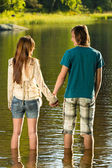 Teenage couple standing in water holding hands — Stock Photo