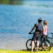 Young cyclist couple watching the lake — Stockfoto