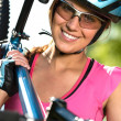 Female cyclist carrying her bike — Stock Photo