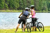 Young bikers at lake watching the forest — Stock Photo