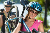 Sporty teens carrying their mountain bikes — Stock Photo