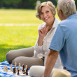 Senior wife and husband playing chess outdoors — Stock Photo