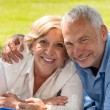 Happy retirement senior couple lying in grass  — Stock Photo