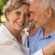 Elderly wife and husband cuddling outdoors — Stock Photo
