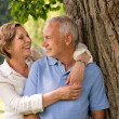 Stock Photo: Happy pensioner couple cuddling outdoors