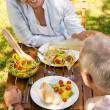 Retired couple eating and drinking outdoors — Stock Photo