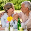 Retired couple sitting at table holding hands — Stock Photo