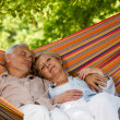 Senior couple relax sleeping in hammock — Stock Photo