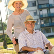 Stock Photo: Wealthy senior min wheelchair with wife