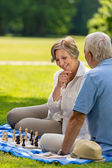 Elderly friends couple playing chess outdoors — Stock Photo