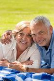 快乐退休高级情侣躺在草 — 图库照片