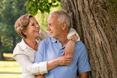 Happy pensioner couple cuddling outdoors — Stock Photo