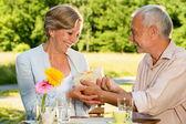 Retired Caucasian couple holding gift — Stock Photo