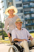 Wealthy senior man in wheelchair with wife — Stock Photo