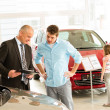 Car agent showing vehicle to young family — Stock Photo