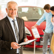 Stock Photo: Portrait of salesmin car retail store