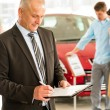 Stock Photo: Caucasian salesman in car showroom