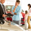 Young man discussing with car agent — Stock Photo #29786787