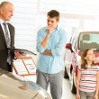 Car dealer offering vehicle to young family — Stockfoto