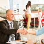 Customer and car salesman shaking hands — Stock Photo